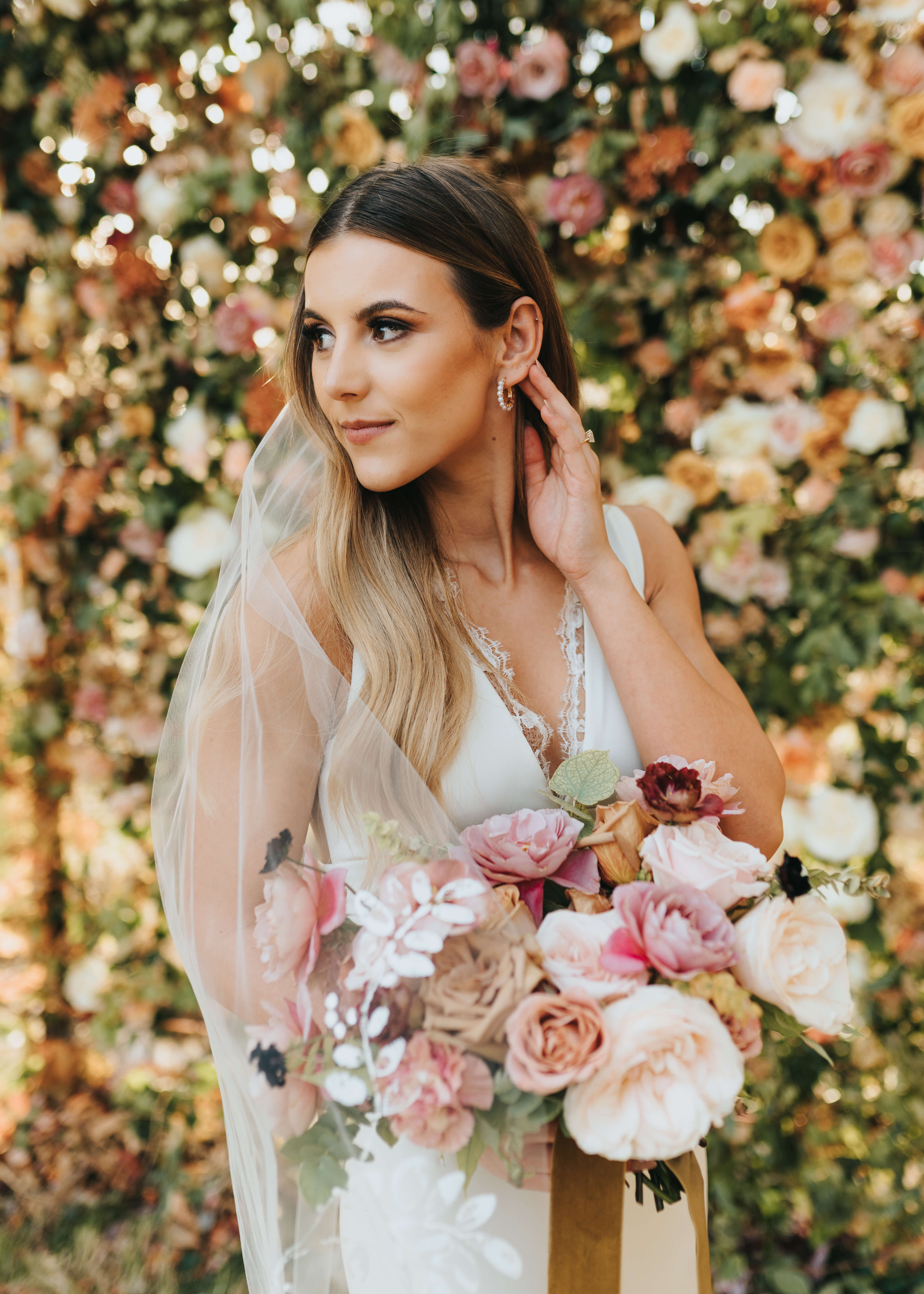 bride standing by pink floral wall