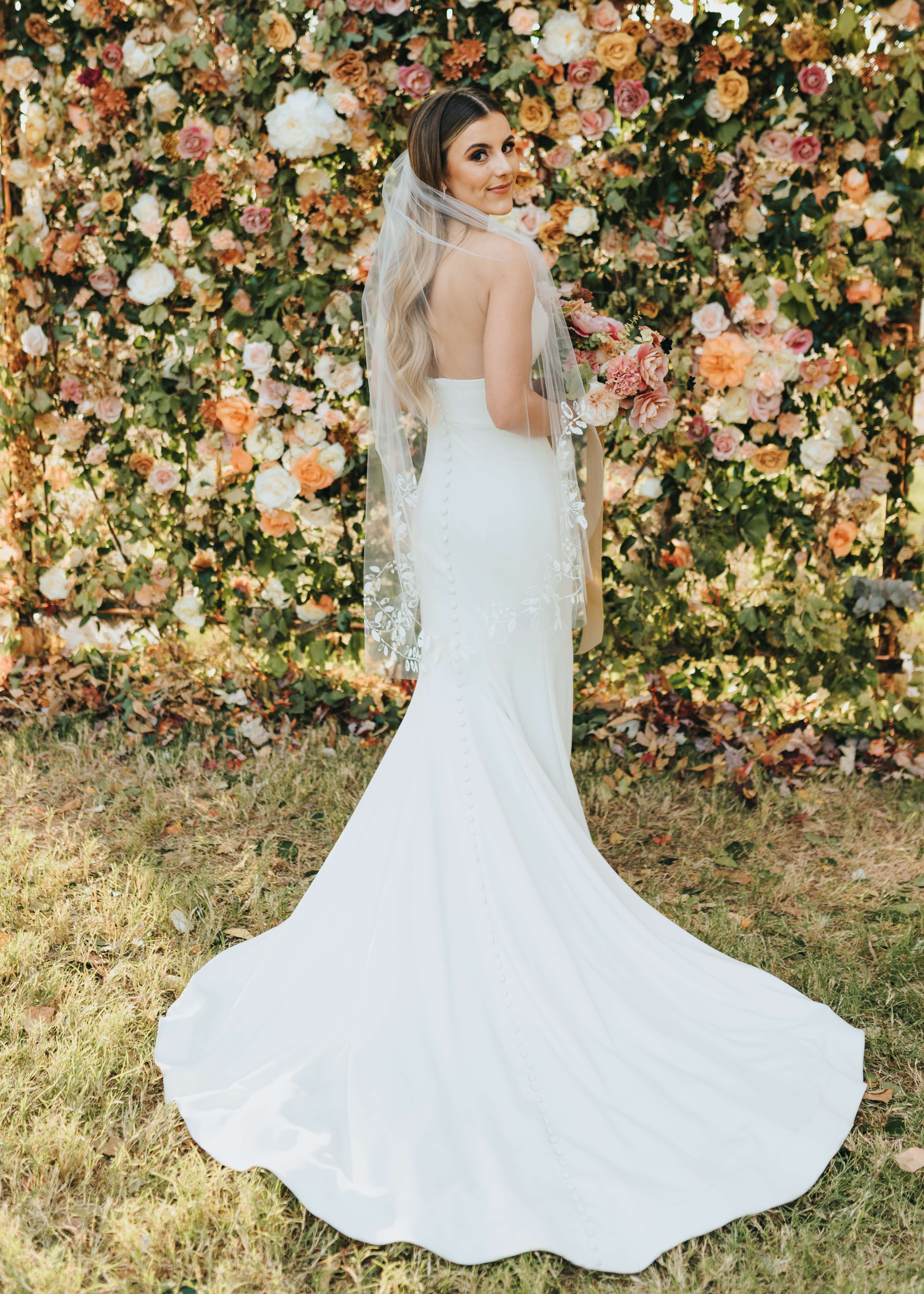 backless dress shot in front of floral wall