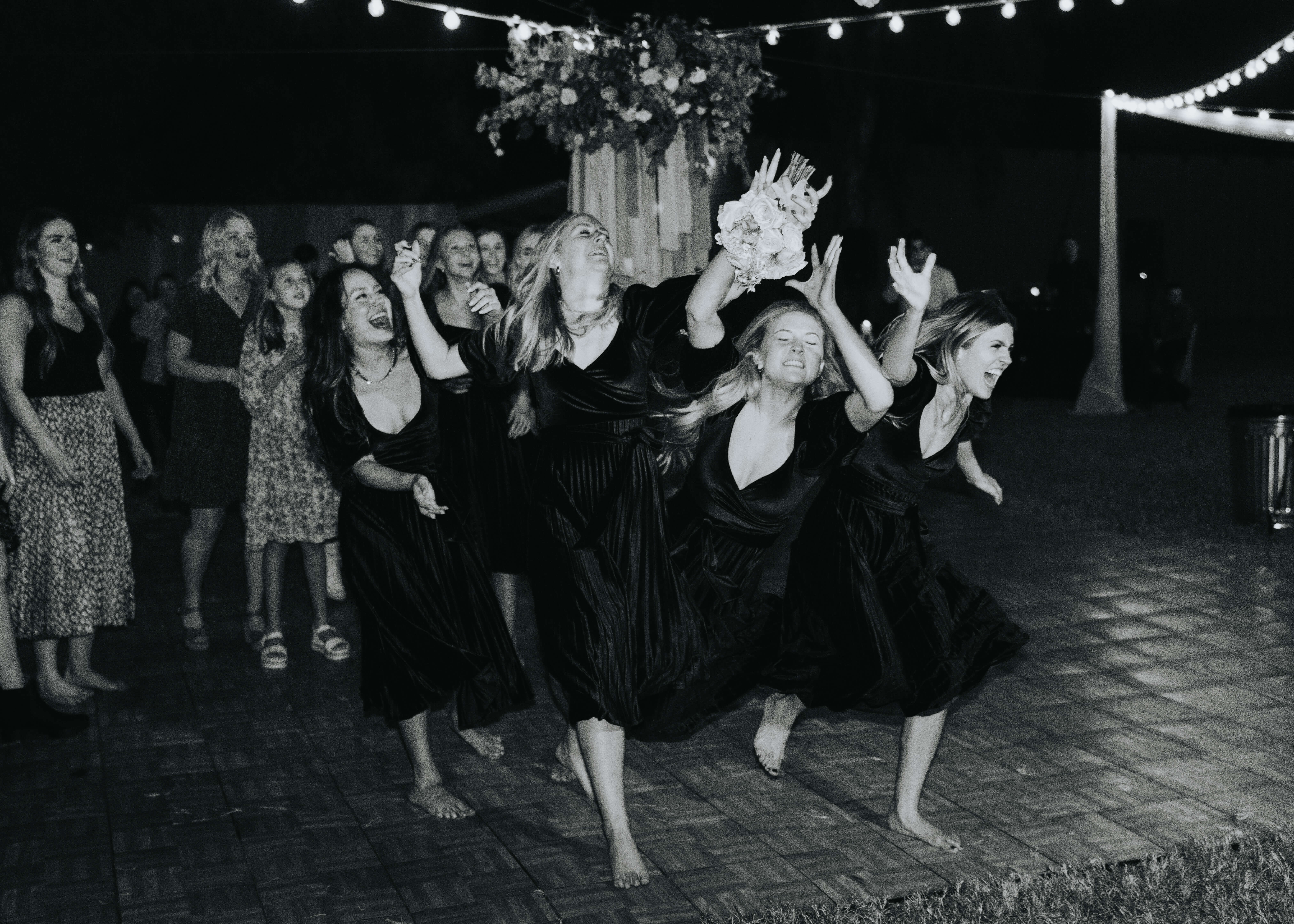 bridal party catching bouquet photo