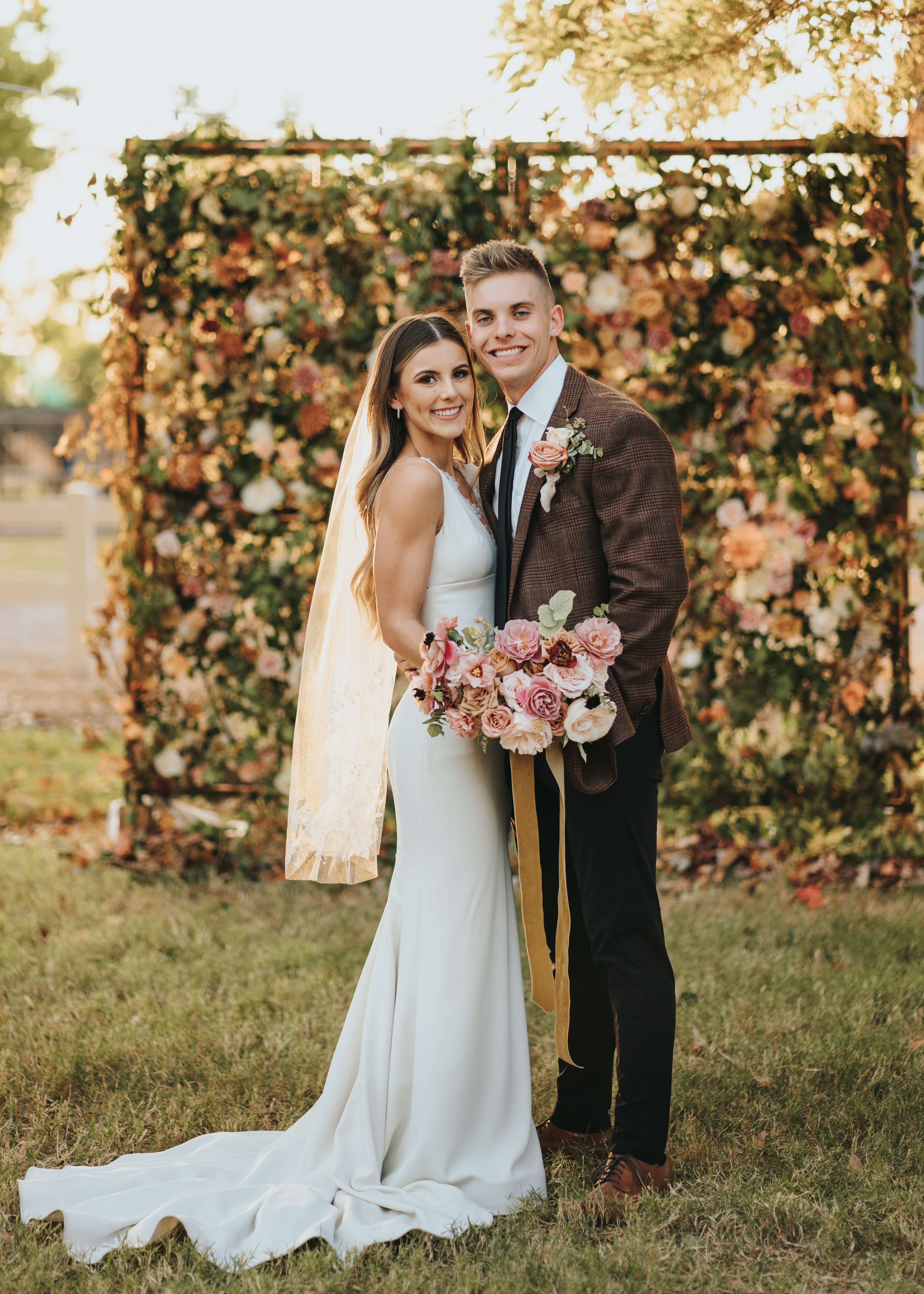 bride and groom by floral wall in arizona