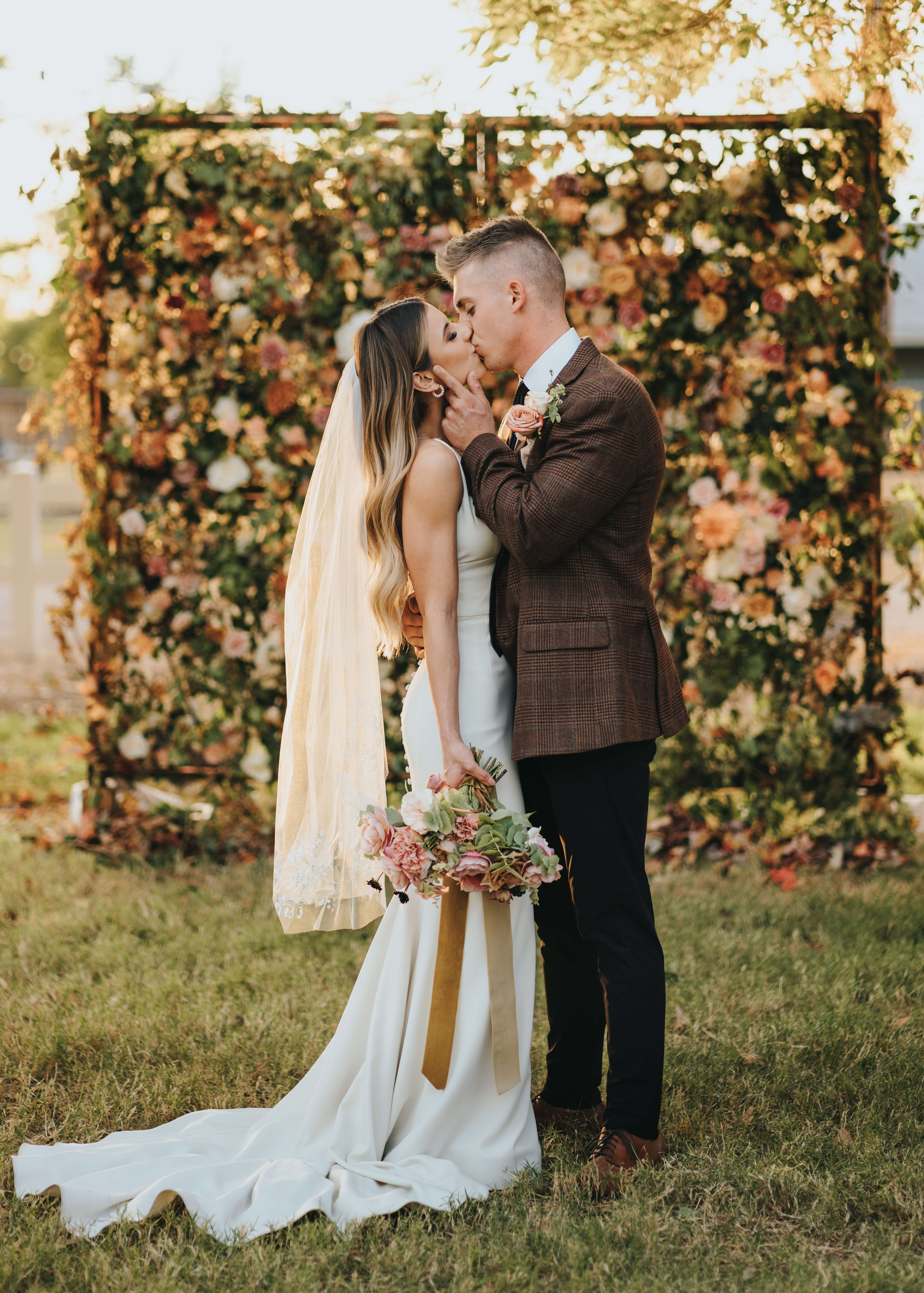 kissing picture of bride in groom on wedding day by floral wall