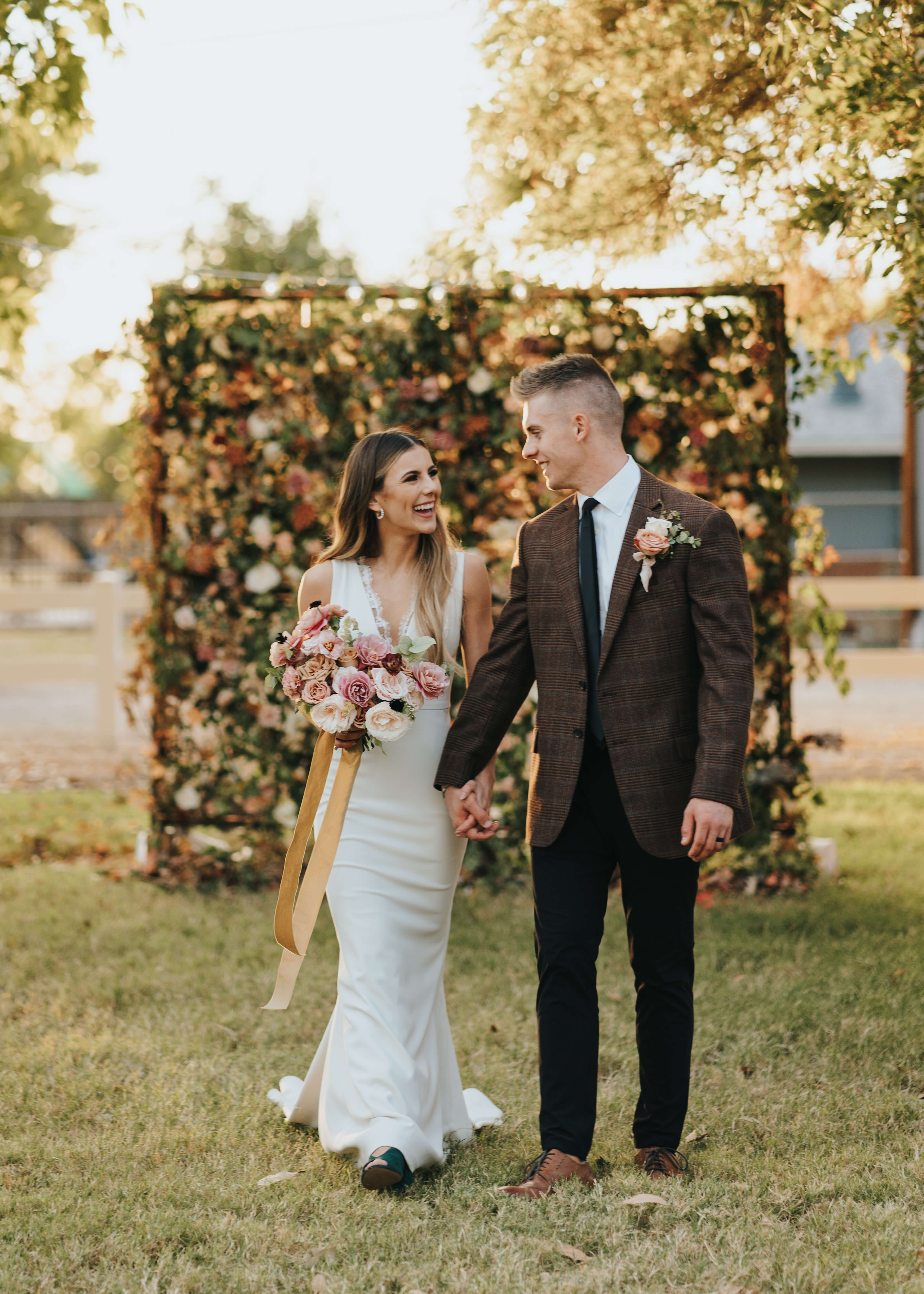 candid photo of bride and groom with floral wall backdrop