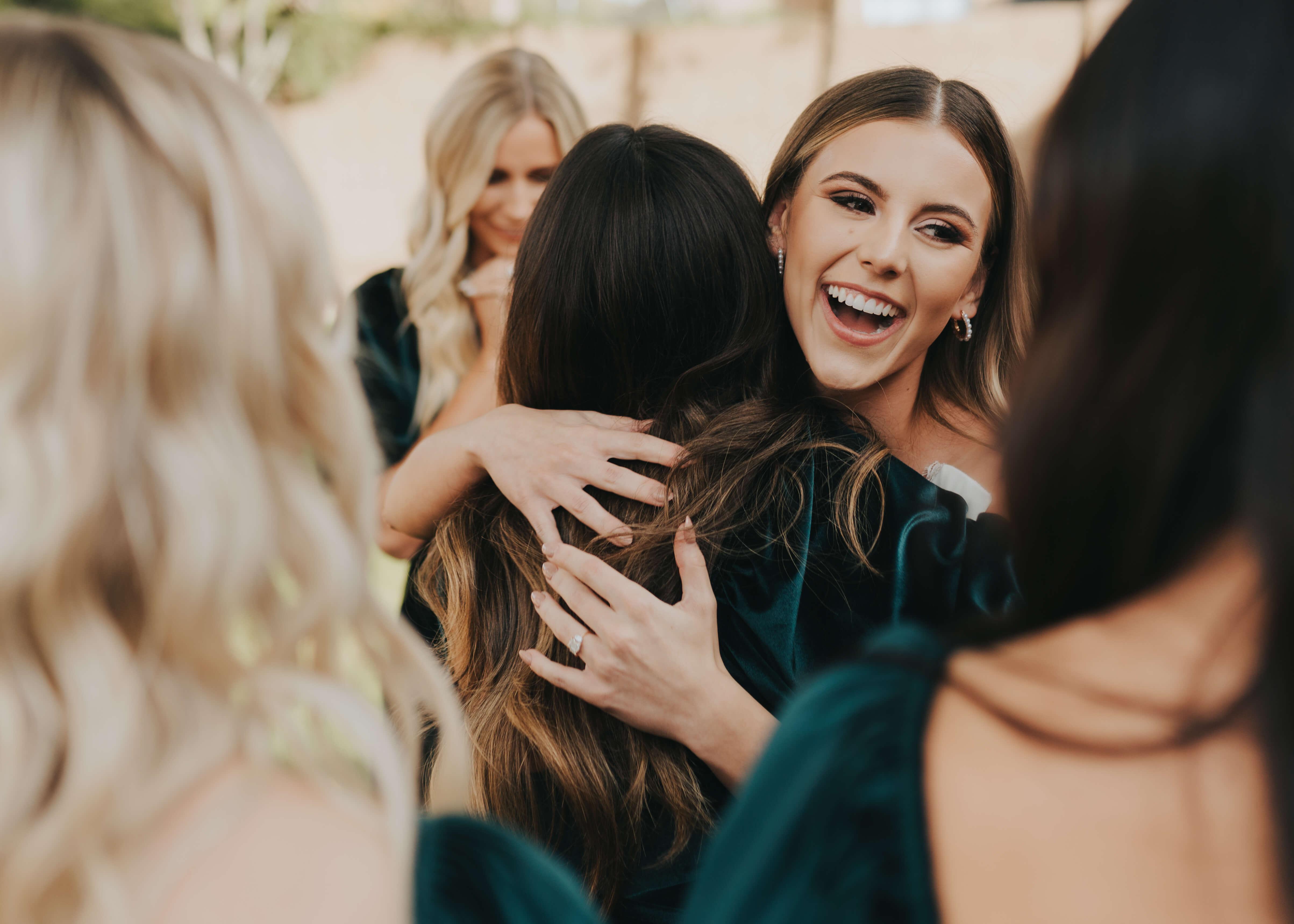 bride hugging bridesmaids candid photo