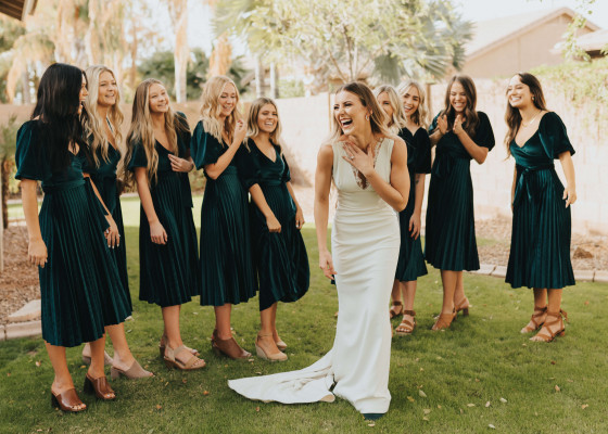 candid photo of bridesmaids in emerald green dresses laughing
