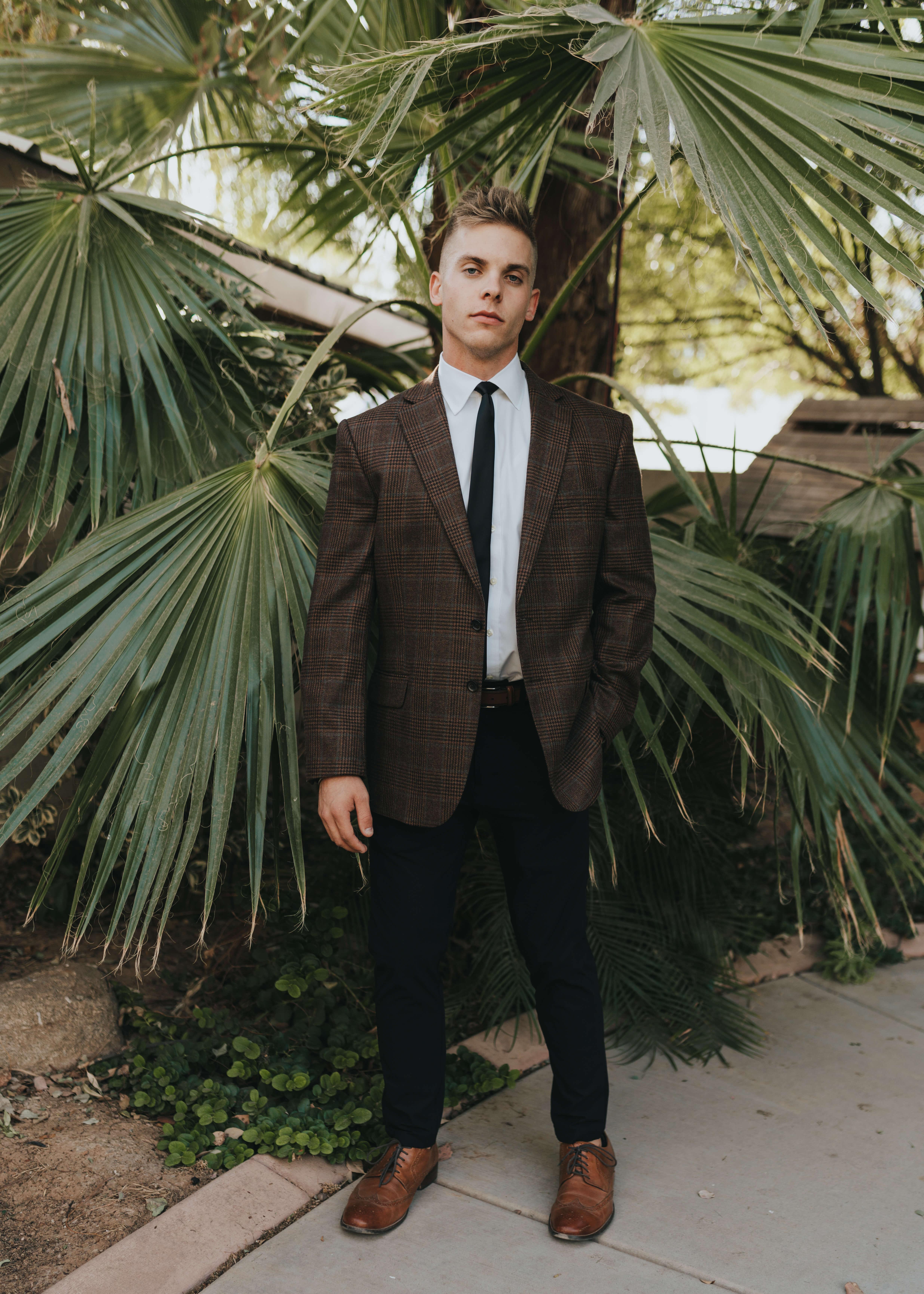 groom in brown tweed suit for wedding day wearing a black tie