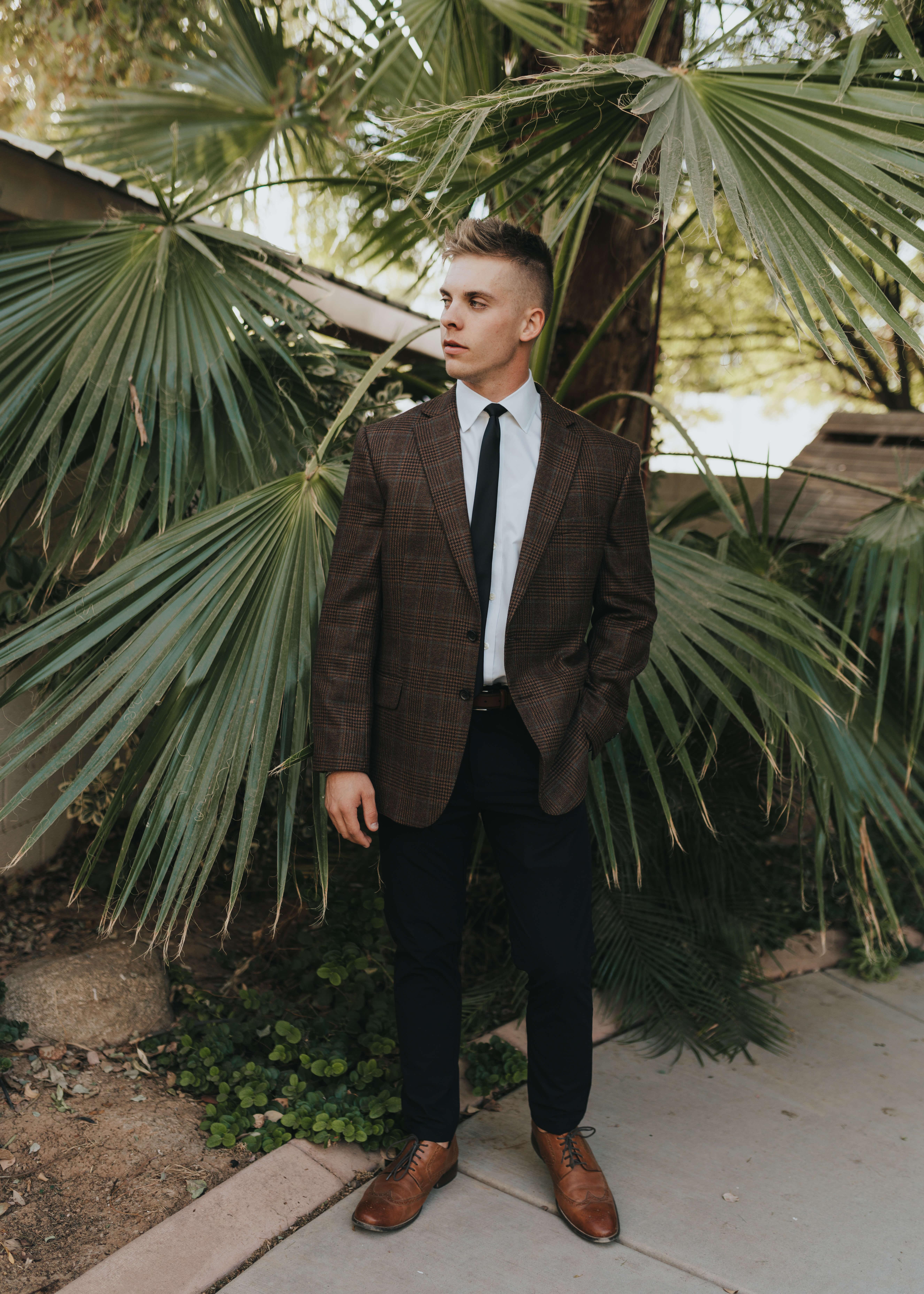 groom poses brown tweed suit black tie