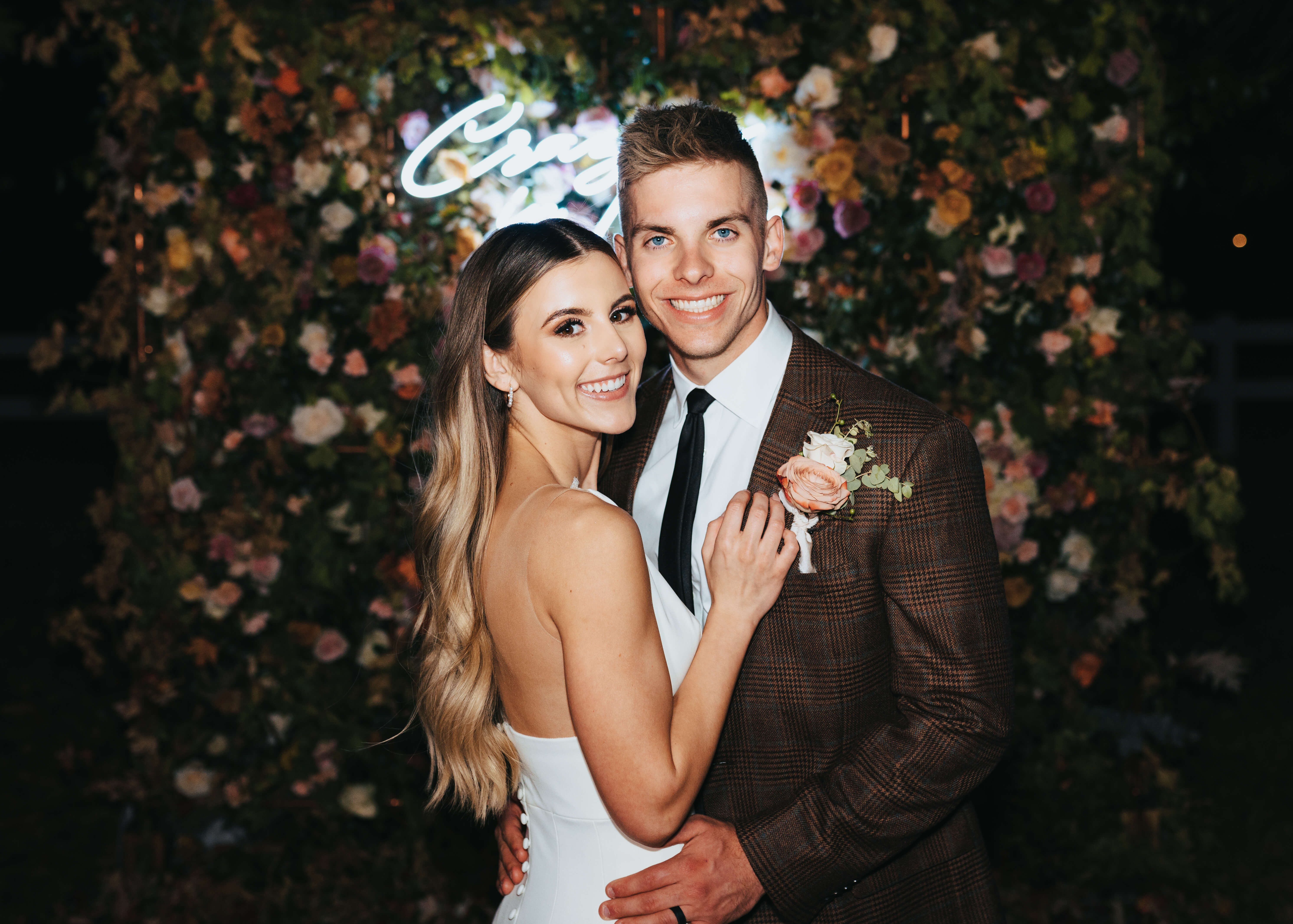 neon sign wedding idea couple in front of floral wall