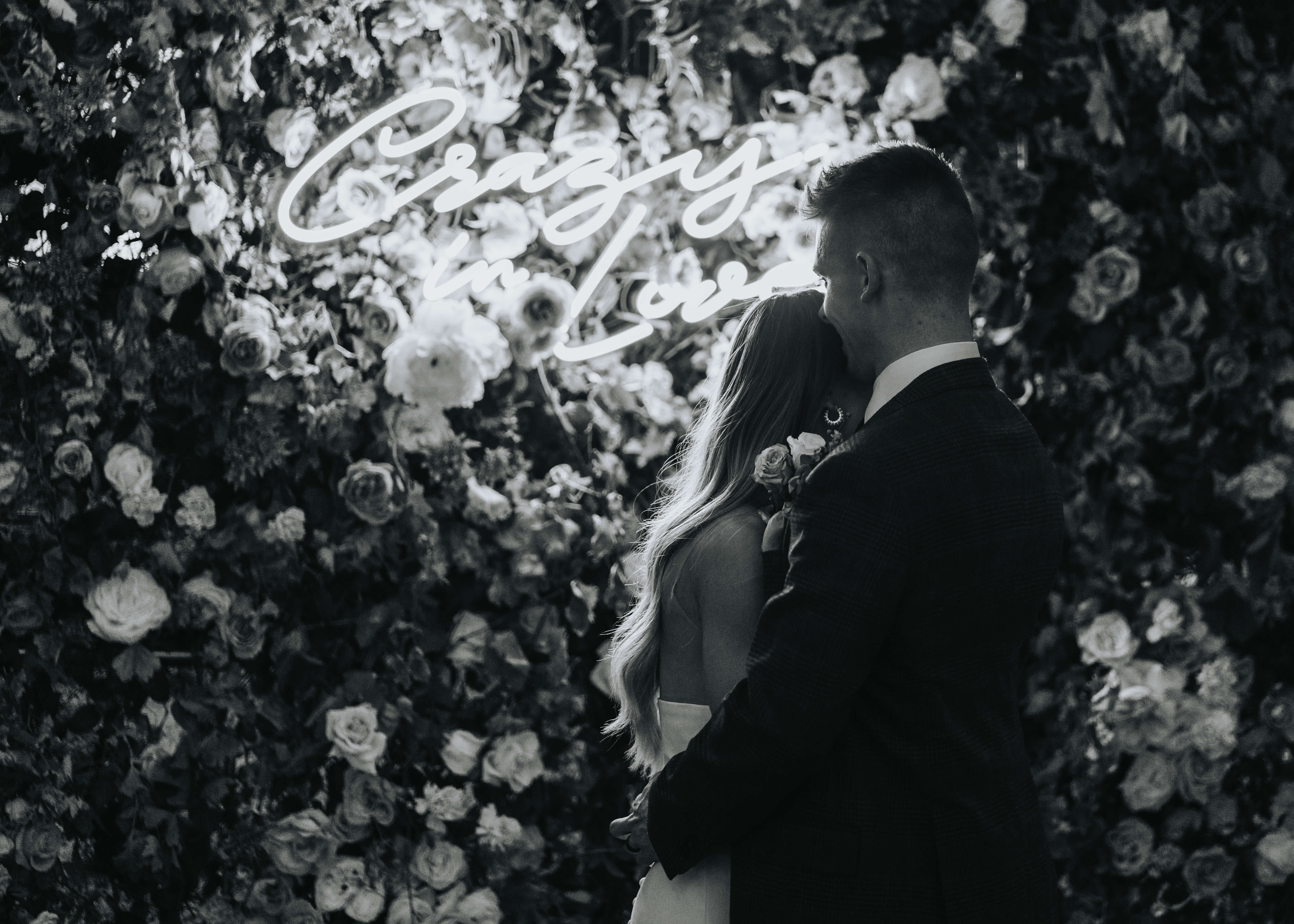 secret vows idea with neon wedding sign on floral wall photo